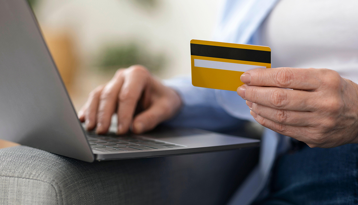 Close up of a woman using a laptop with a credit card in her hand