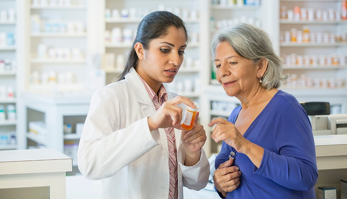 A pharmacist holding a pill bottle talking to a customer