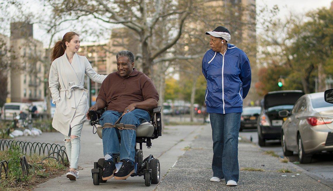 Two women walking down a city sidewalk with a man in a motorized wheelchair