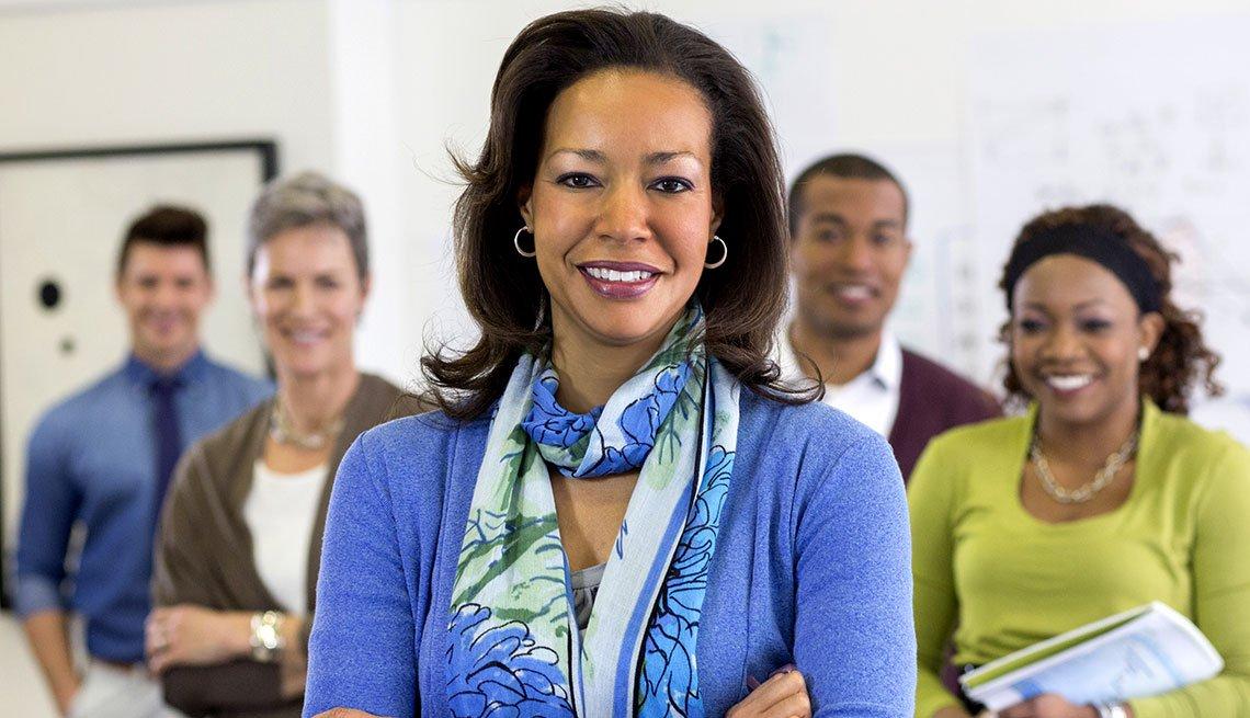 Grupo de 5 personas sonriendo y vestidas con ropa casual de oficina