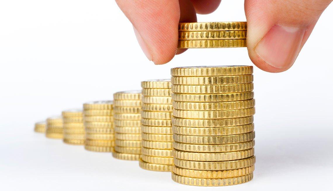 Una mano creando columnas de monedas