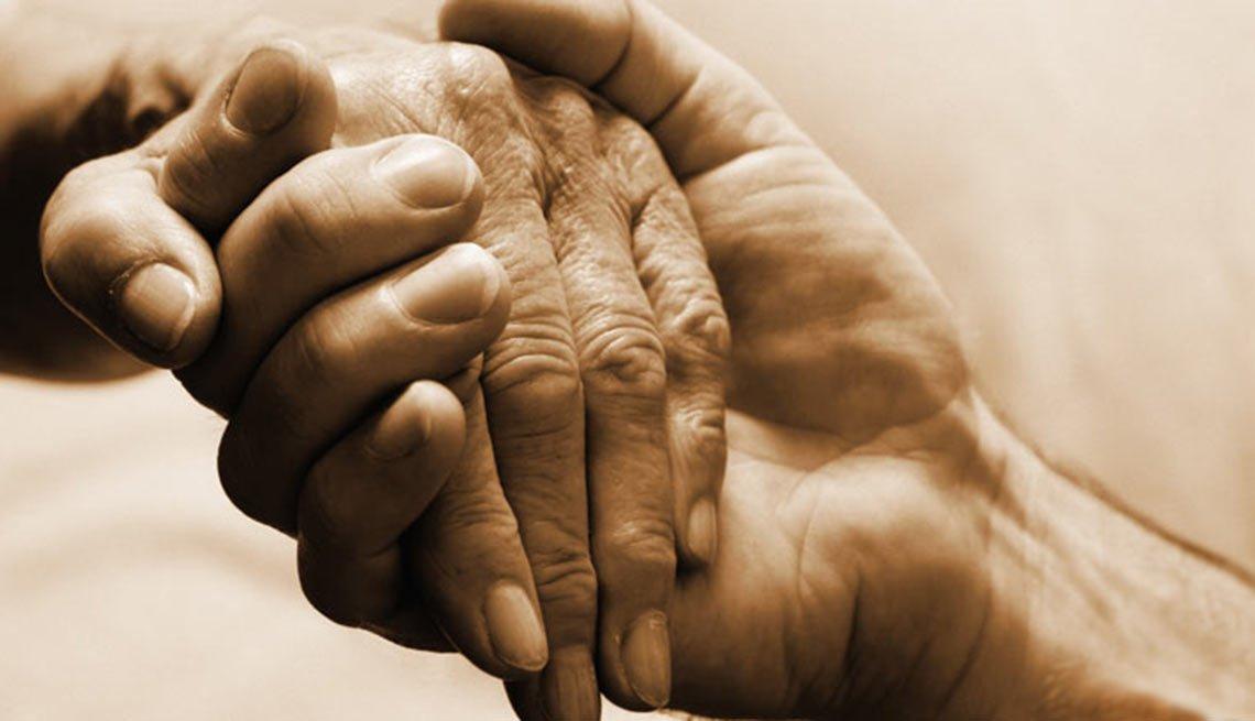 Manos de una persona joven y una persona mayor unidas
