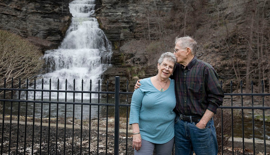 Man and woman hugging, pose in front of a waterfall