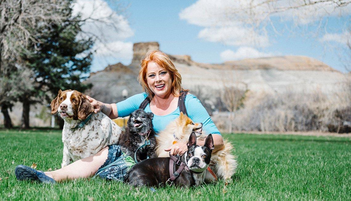 Mujer fotografiada con sus perros en el pasto