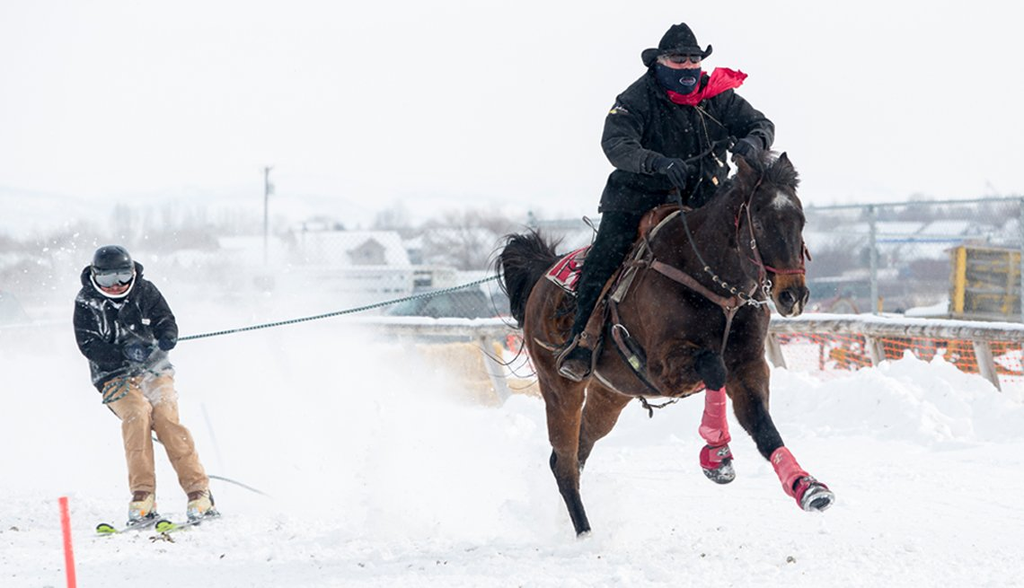 man on a horse towing a skiier. this sport is called skijoring.