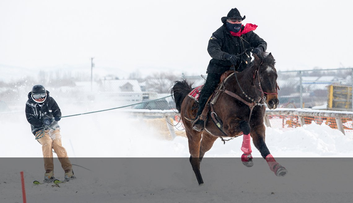 skijoring - a horseback rider towing a skiier in the snow