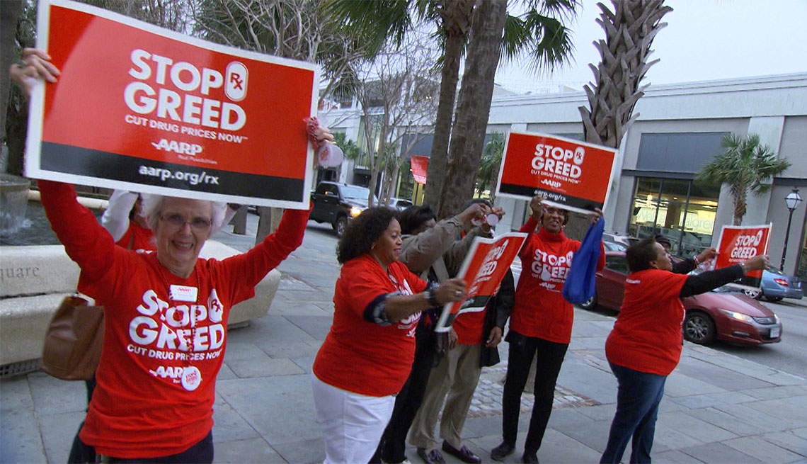 people on sidewalk hold up  a a r p stop rx greed signs as cars pass by
