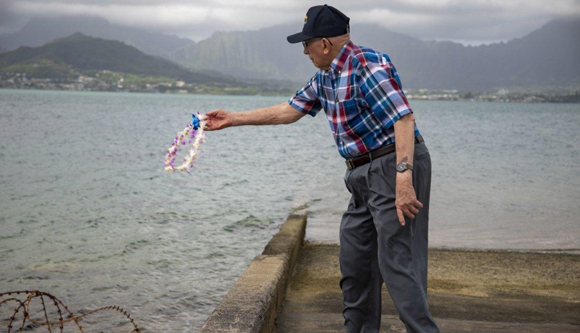 Hugh McNaughton throwing a flower wreath into the pacific ocean