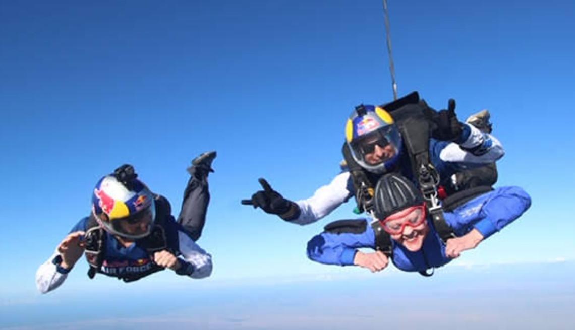 Un paracaidista solitario a la par de dos paracaidistas tándem en caída libre