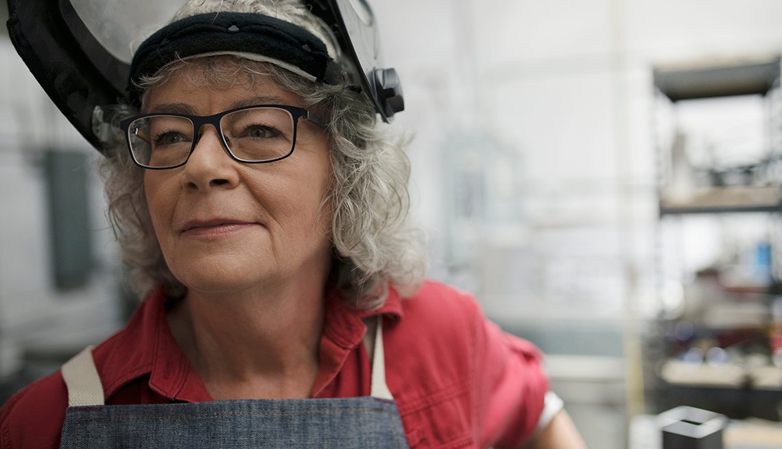 a female welder over age 50 is smiling at work with her face mask flipped up to show her face
