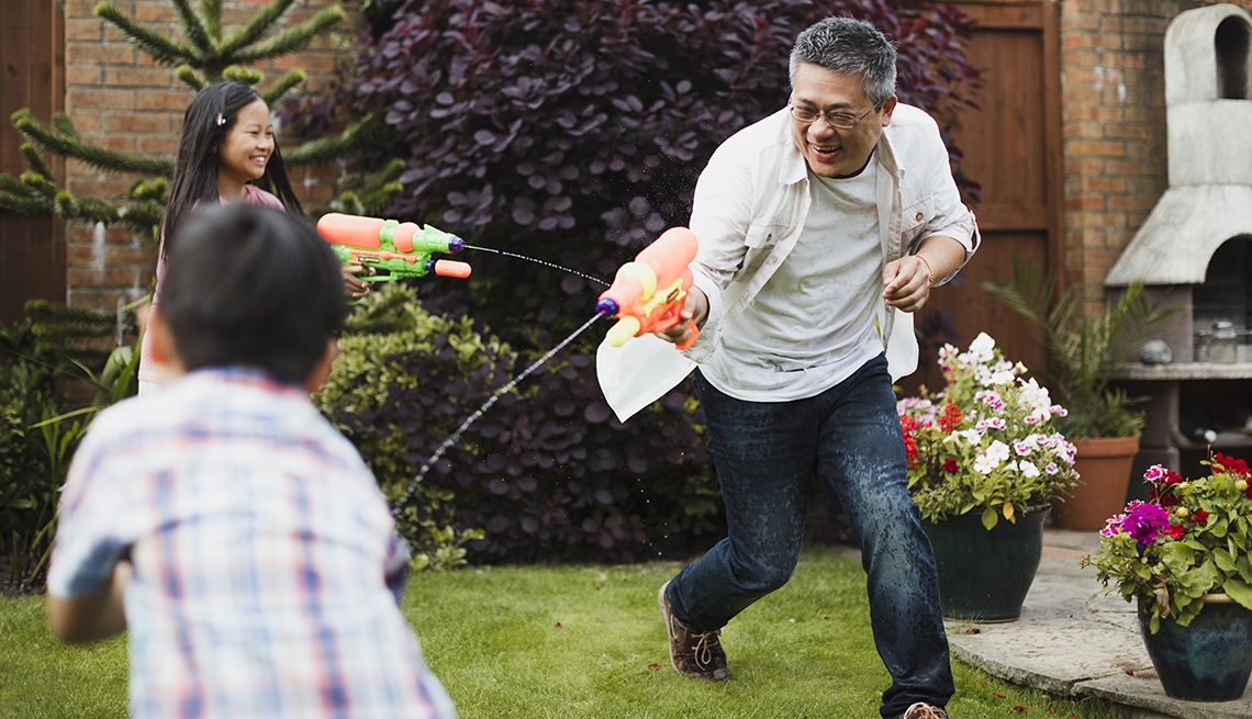 grandfather having a fun squirt gun waterfight with two grandchildren in his yard