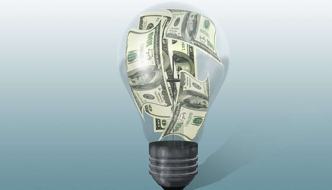 A light bulb with money inside