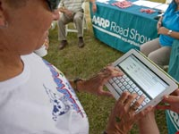 A woman learns how to become a member of AARP online at the AARP Roadshow on July 29, 2011 at the Lucas Oil Raceway in  Indianapolis, IN