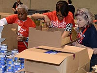 Volunteers box donated food for delivery to the Greater Boston Food Bank as part of the AARP Foundation Drive to End Hunger meal packing activity during Life@50+ Boston.