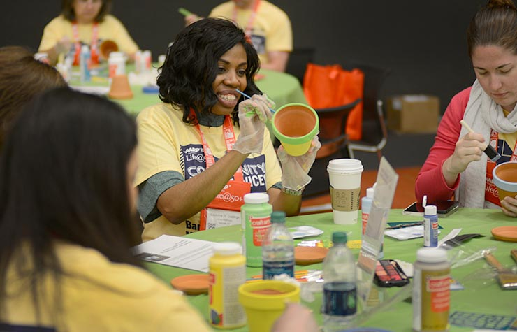 AARP volunteers decorated flower pots and then fill them with potting soil and hardy seedlings during the Life@50+ Boston Community Day of Service.