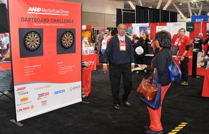 Attendees used their dart-throwing skills to try to win a music docking station at the AARP Media Road Show, part of Life@50+ Boston.