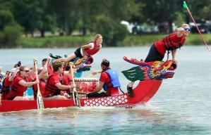 Gente remando en un bote con figura de dragón