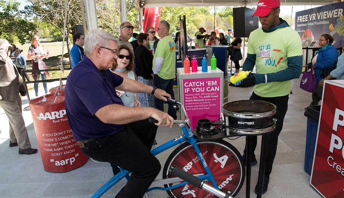 Hombre mayor creando spin-art montado en una bicicleta con varios expectadores detrás.