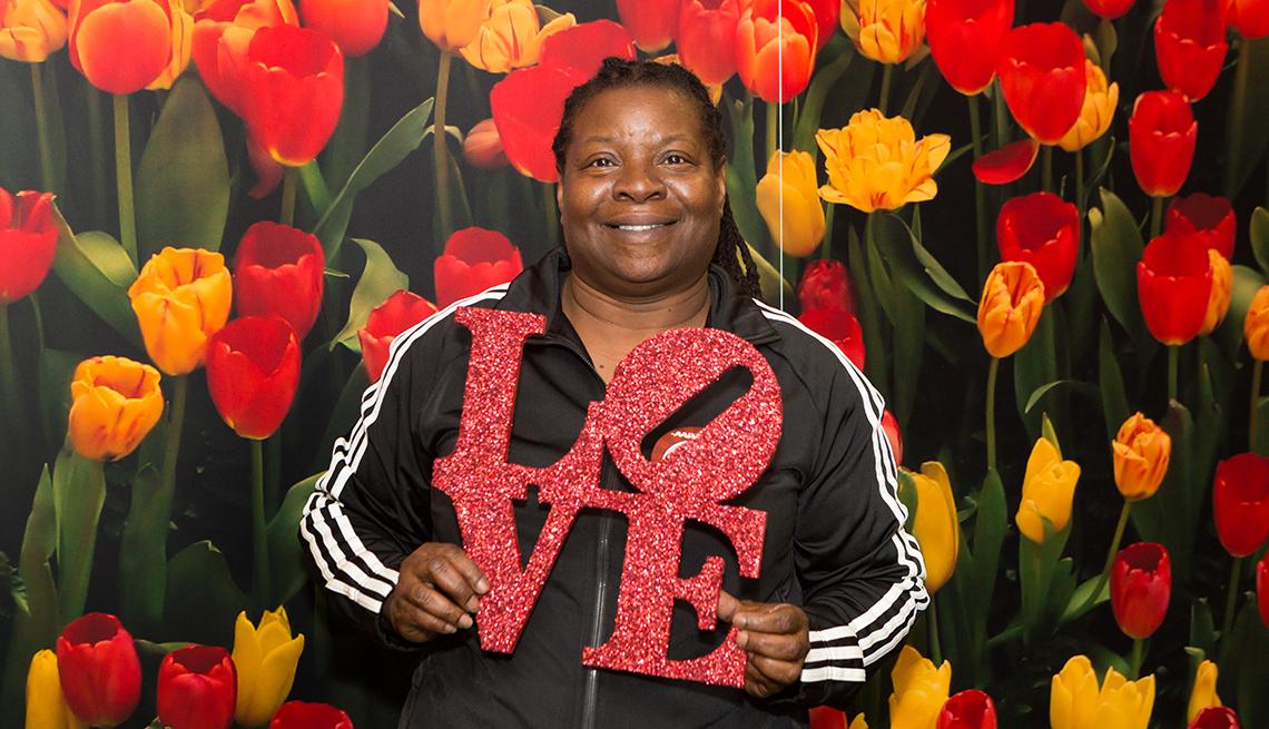 Mujer sosteniendo el love (amor) logo de Filadelfia con flores detrás de ella.