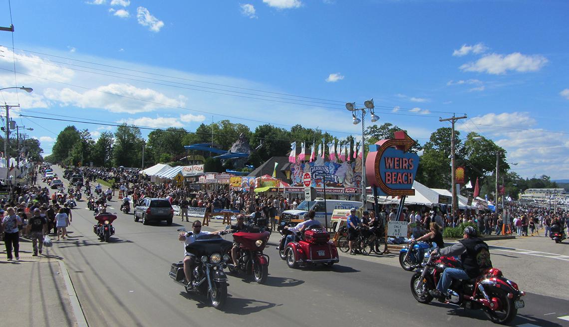 Motocicletas pasando en la carretera entre las tiendas de feria durante el Laconia Motorcycle Rally en New Hampshire