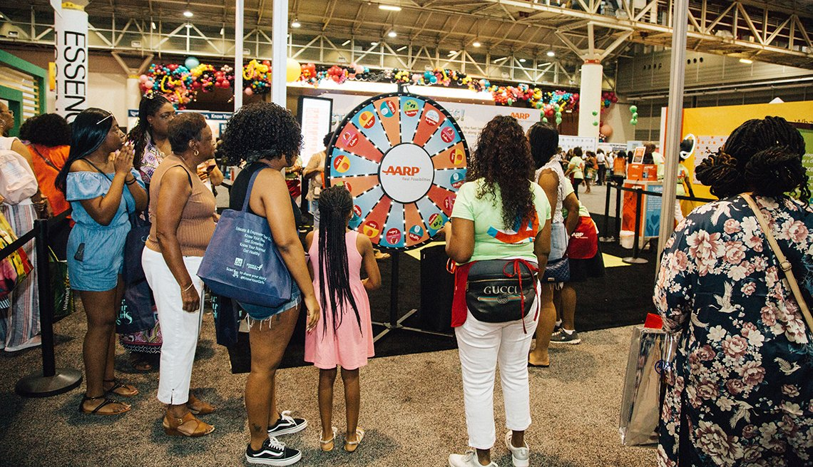 A group of people watching a prize wheel spin at the A A R P block party during the Essence festival