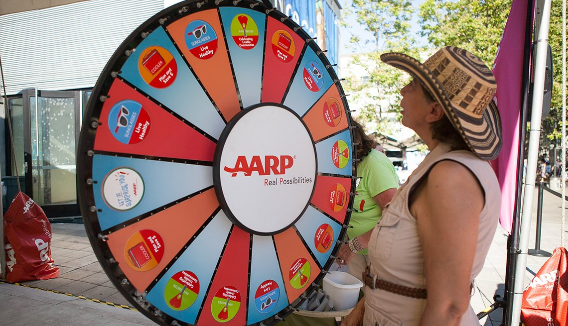 Woman spinning a prize wheel at an A A R P block party event