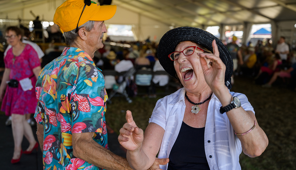 A couple dancing together and laughing during the New Orleans Jazz Festifval