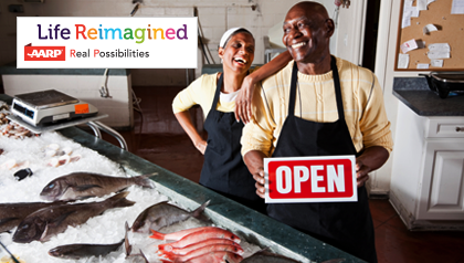 Senior couple standing behind counter of fish store selling seafood. Small Business Resource Center