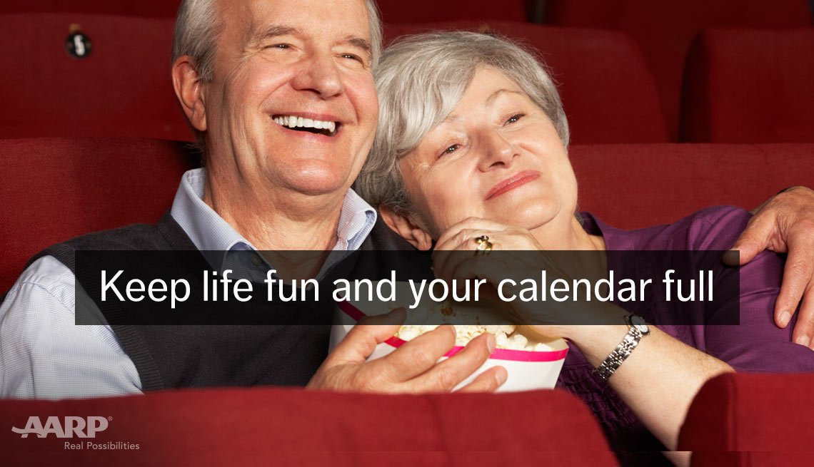 A caucasian middle aged couple eat popcorn in movie theater with text that reads keep life fun and your calendar full.