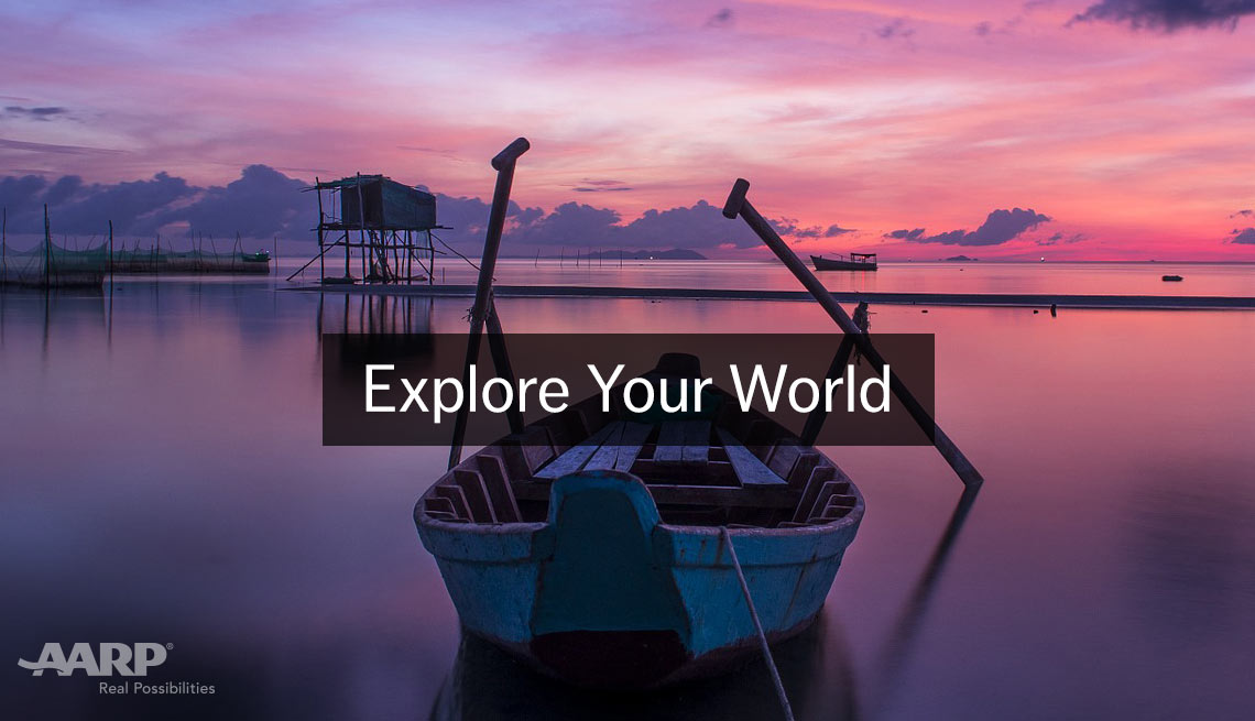 item 5 of Gallery image - Explore Your World, A A R P Real Possibilities, Colorful sunset reflected in still water. wooden row boat with oars in foreground center