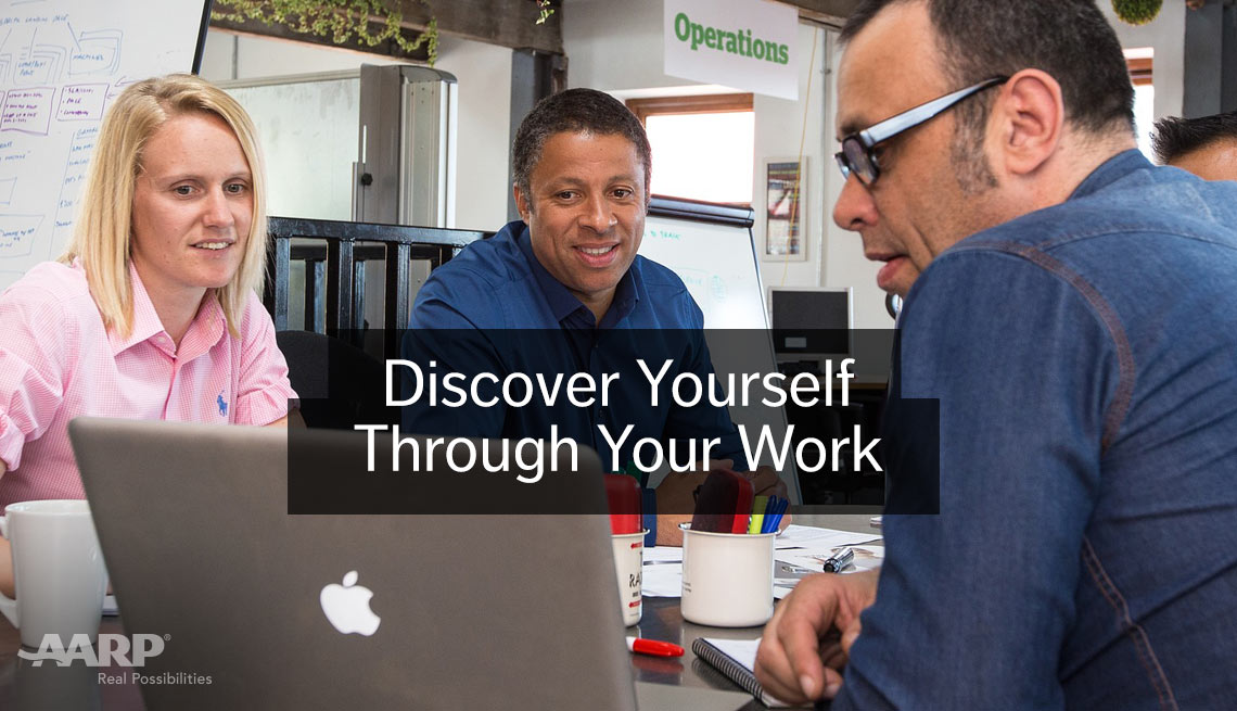Discover yourself through your work. Two seated men and a woman look at apple laptop screen in office