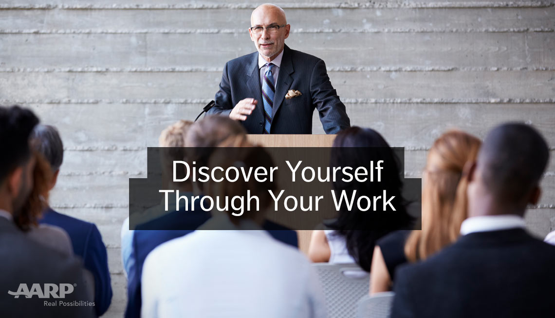 Discover yourself through your work. Caucasian man in suit stands talking to seated group of younger people