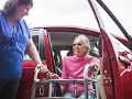 Qué deberían tener los automóviles para cuidadores - Mujer baja de un carro ayudada por un caminador