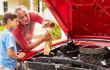 Abuelo y niño trabajando en el motor de un carro - Cómo hacerle mantenimiento a tu viejo automóvil