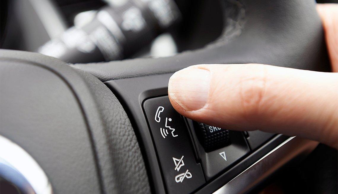 La mano de una persona controla el botón de bluetooth en el volante de un automóvil.