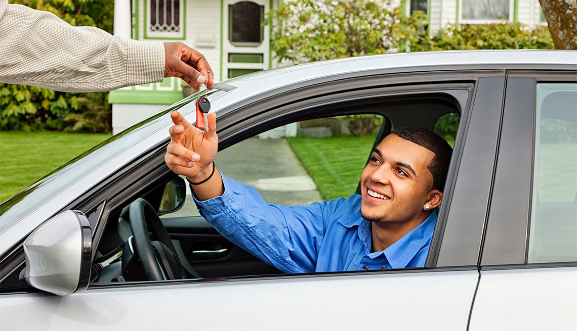 Imagen de joven al volante de un deportivo plateado, tomando las llaves con una sonrisa.