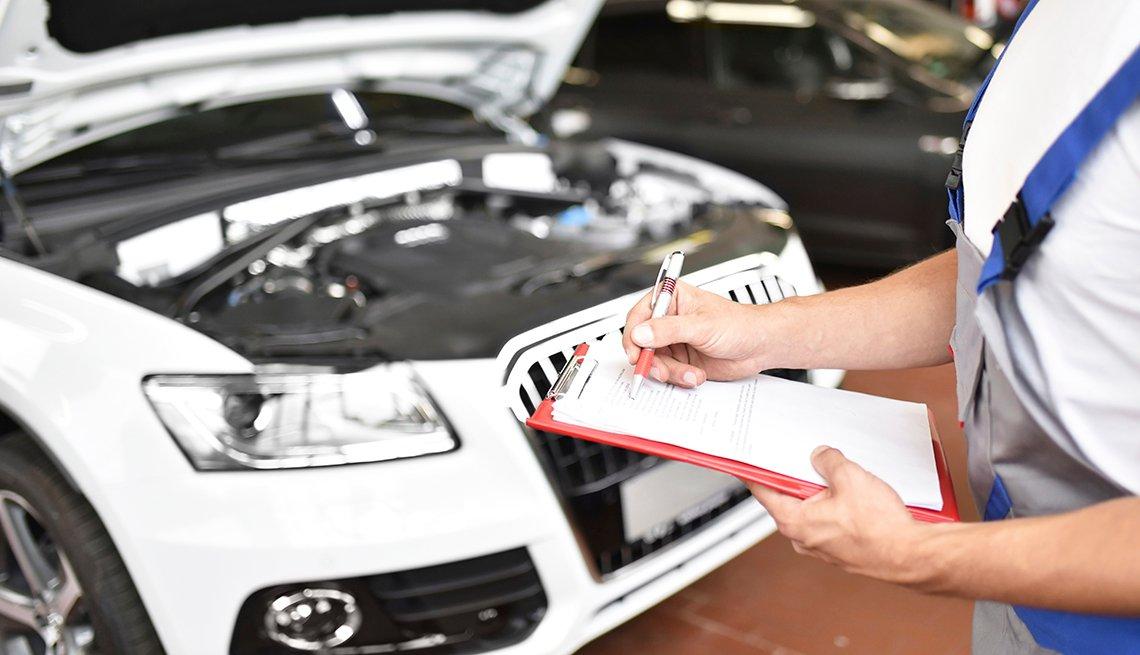 Mecánico de automóviles sosteniendo un portapapeles en un garaje.