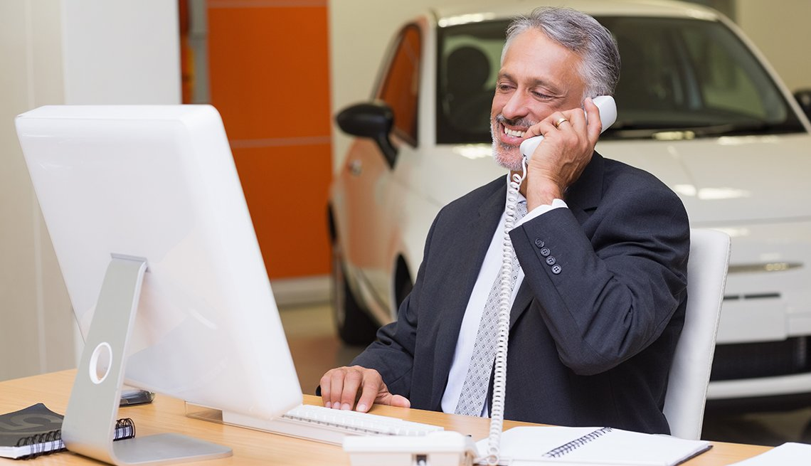 car salesman on the phone at a dealership