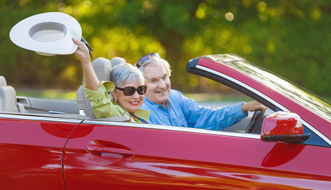 couple driving red convertible