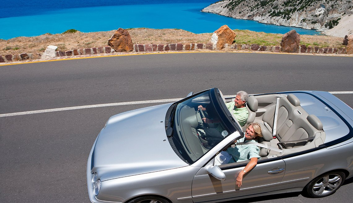 couple driving silver convertible near the ocean