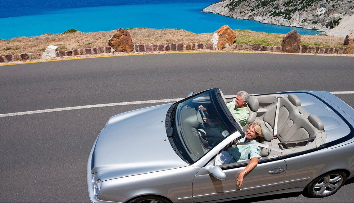 couple driving silver convertible near the ocean