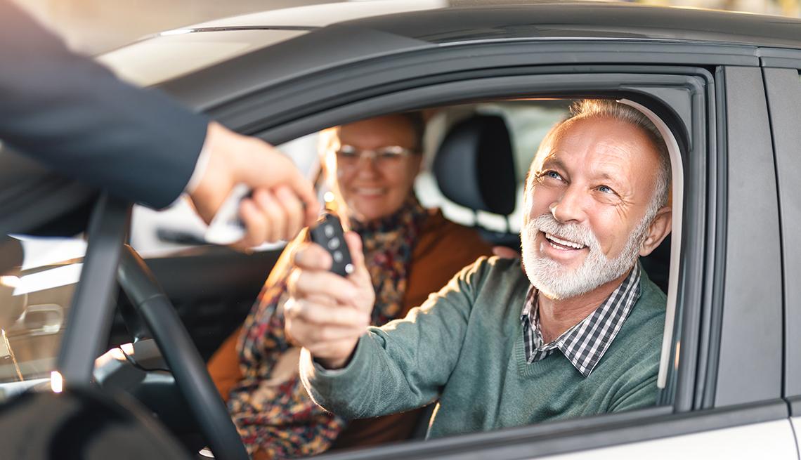 Pareja de adultos mayores en un automóvil, recibiendo las llaves de su auto nuevo.