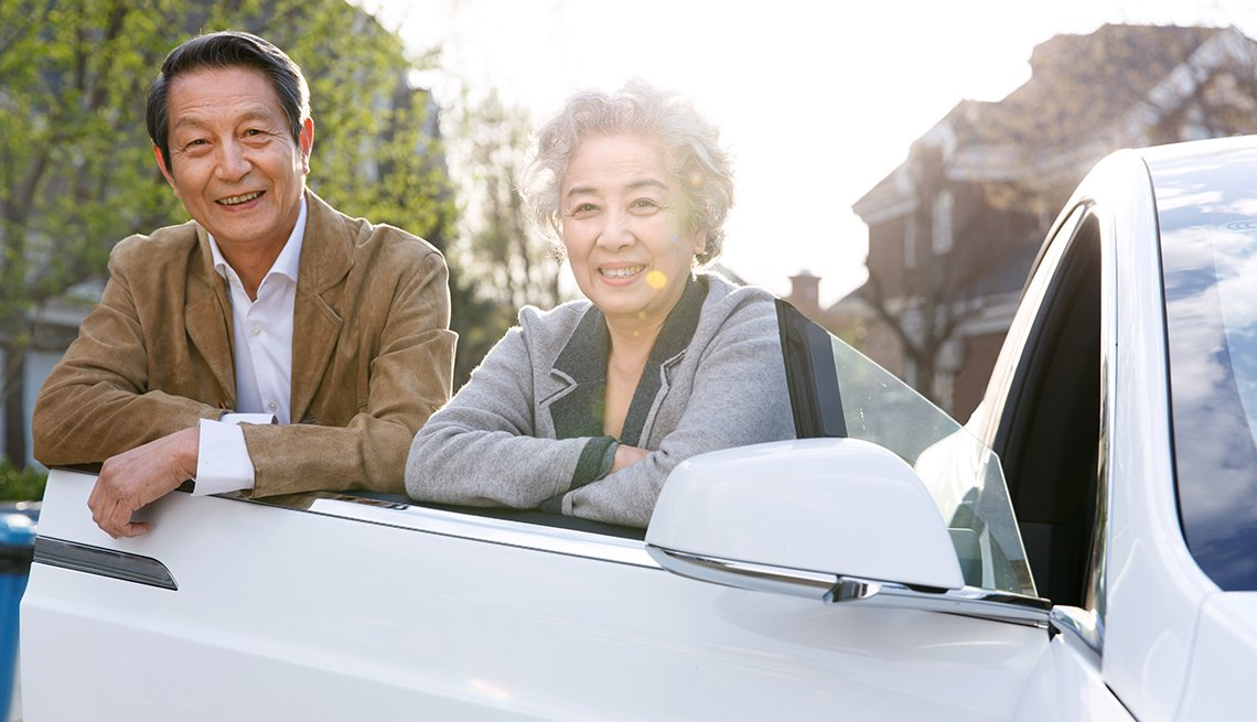 Older couple standing next to car door