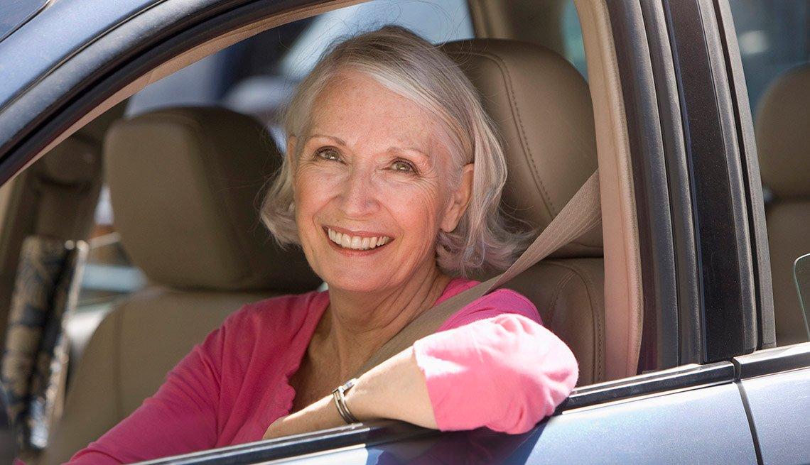 Mujer mayor sonríe mientras está sentada en un auto.