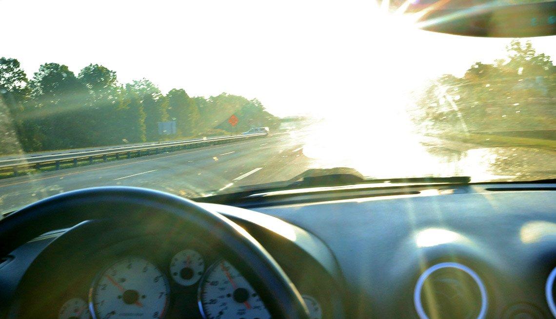 El resplandor del sol se ve desde un auto en el horizonte.