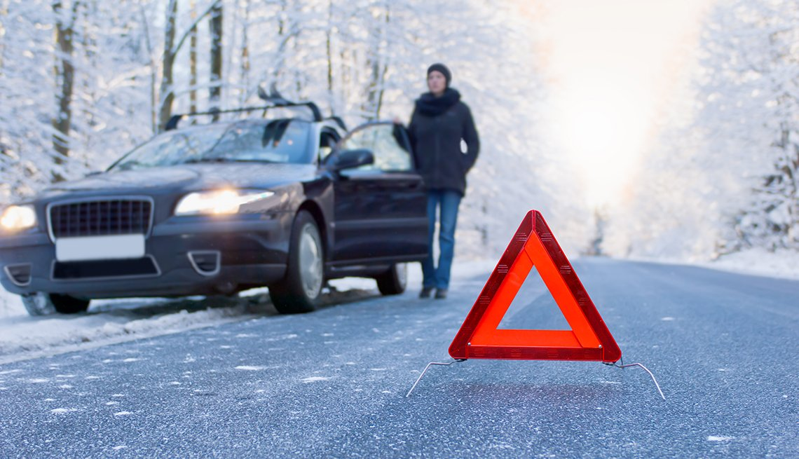 Car breakdown on a country road in winter. Woman standing beside her car and waiting for help.