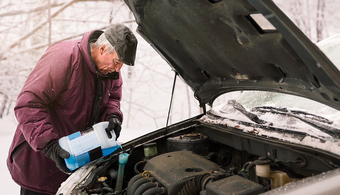 Senior man pouring Antifreeze windshield washer liquid during winter snow storm.