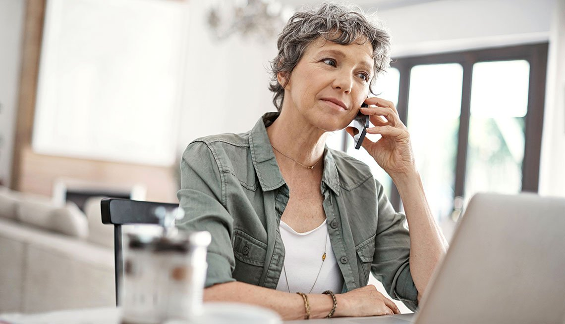 Shot of a mature woman making a phone call while working on her laptop at home