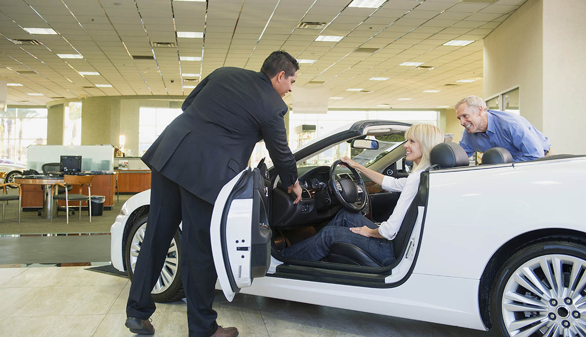 couple sitting in a convertible at car dealership