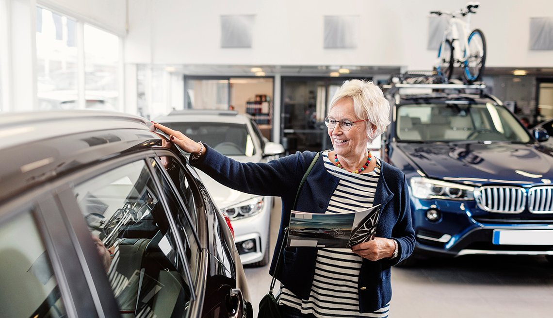 woman looking at car in showroom